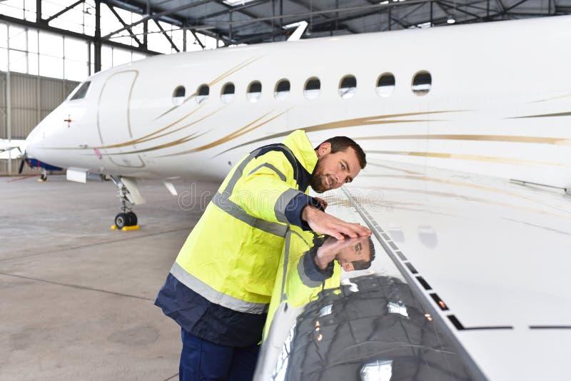 Flugzeugmechaniker kontrolliert und überprüft die Technologie eines Jets herein stockfotos