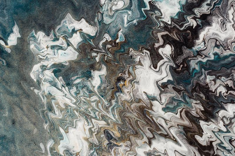 Fluid Art. Abstract wavy background or texture. White, black and blue zigzags. Noise of gold particles.  stock image