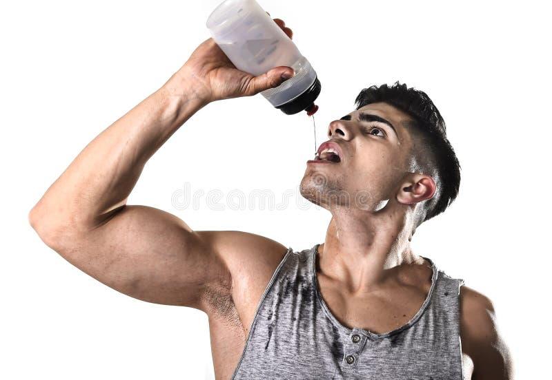 Fluide de versement potable assoiffé de bouteille de retenue d'eau de jeune homme de sport sportif sur le visage en sueur photo stock