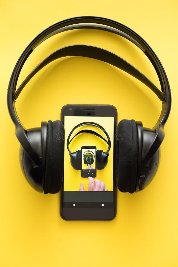 Fluir concepto de la música auriculares inalámbricos y un teléfono móvil en fondo amarillo fotografía de archivo libre de regalías