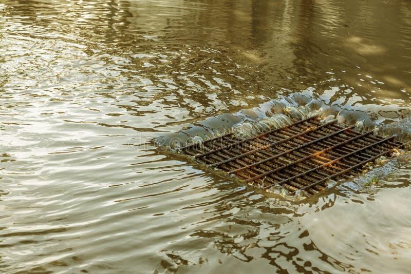 Flujo de agua durante las fuertes lluvias y obstrucción de las aguas residuales de la calle El flujo de agua durante un huracán f imagen de archivo