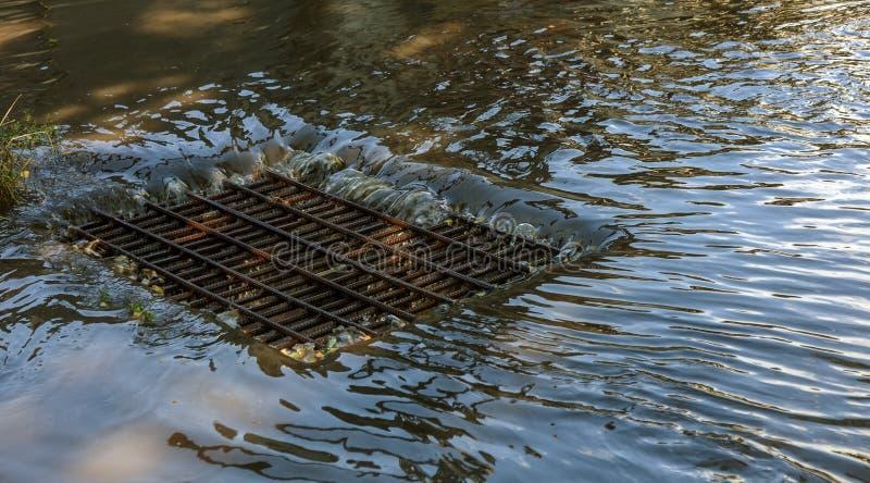 Flujo de agua durante las fuertes lluvias y obstrucción de las aguas residuales de la calle El flujo de agua durante un huracán f fotografía de archivo