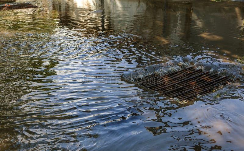 Flujo de agua durante las fuertes lluvias y obstrucción de las aguas residuales de la calle El flujo de agua durante un huracán f foto de archivo