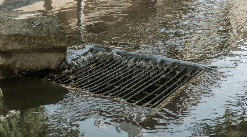 Flujo de agua durante las fuertes lluvias y obstrucción de las aguas residuales de la calle El flujo de agua durante un huracán f imagen de archivo libre de regalías