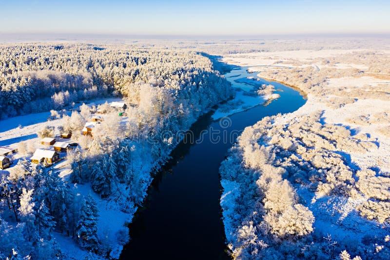 Flujos fluviales a lo largo del valle invernal, paisaje aéreo. El bosque rodea un pequeño pueblo. Concepto de escarcha imágenes de archivo libres de regalías