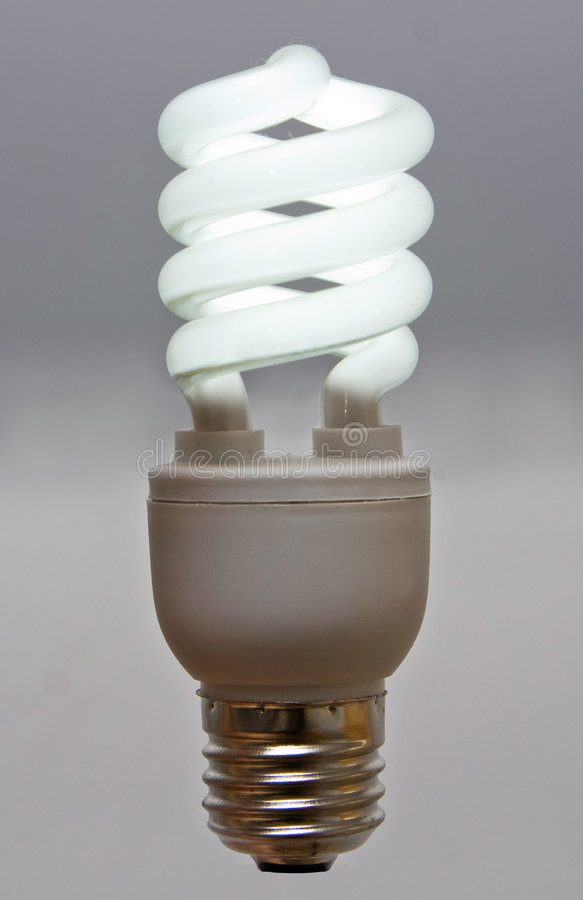 Fluorescent bulb. An environmentally friendly, power and money saving compact fluorescent light bulb on a gray background that glows stock photography