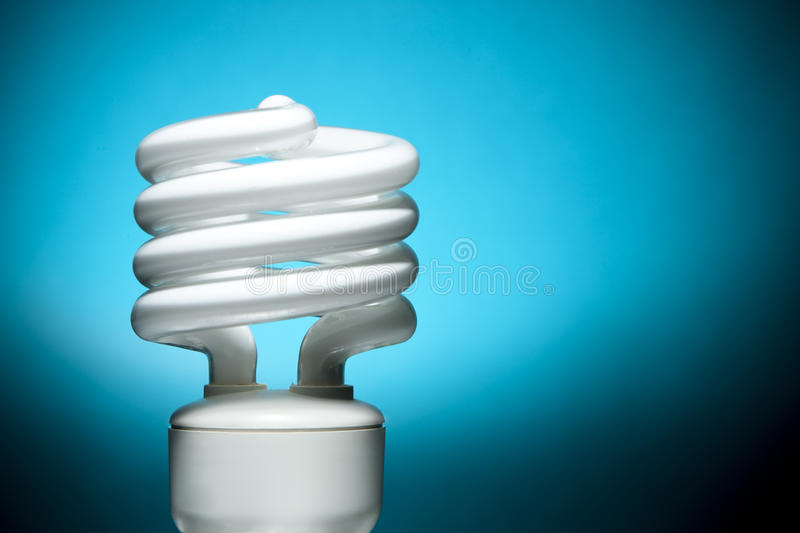 Fluorescent Bulb on Blue Background. Focus on edges of bulb tube and base stock image