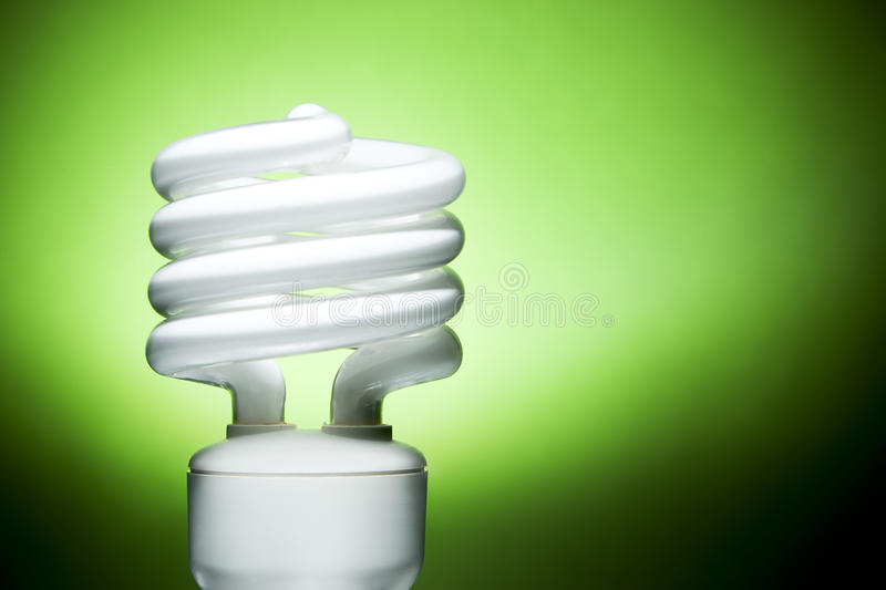 Fluorescent Bulb on Green Background. Focus on edges of bulb tube and base royalty free stock photography