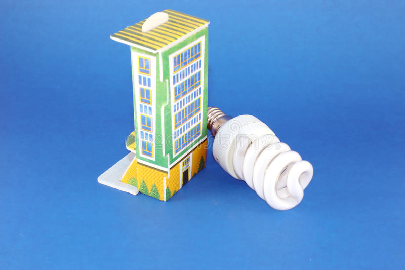 Fluorescent lamp bulb with model of house. Over blue royalty free stock image