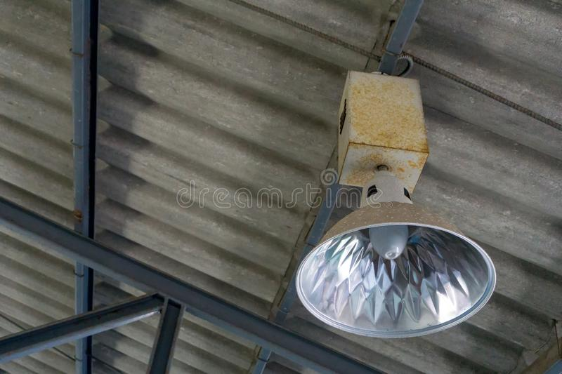 Fluorescent lamp hanging on the roof inside the warehouse. Light bulb installed in the factory stock photography