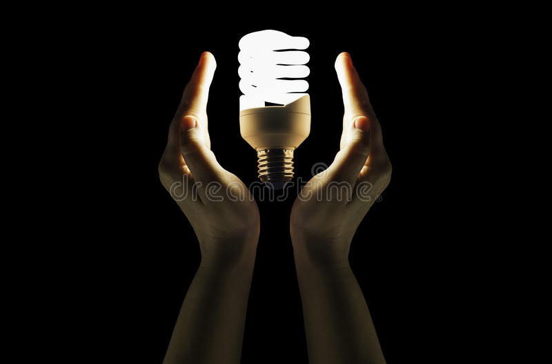 Fluorescent lamp hovering between hands stock photography