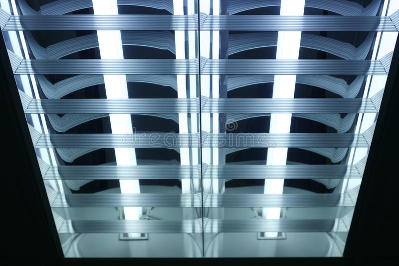 Fluorescent lamp. Office ceiling with built-in fluorescent shining lamp royalty free stock photos
