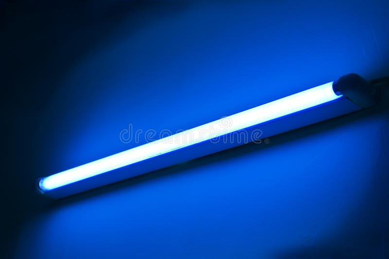 Fluorescent lamp shining on blue colored wall. One fluorescent lamp shining on blue colored wall stock photo