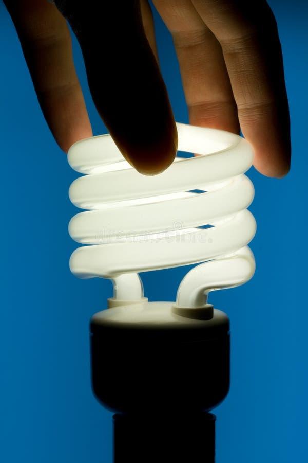 Fluorescent Light Bulb. Hand Installing Energy - Efficient Fluorescent Light Bulb - Blue background stock image