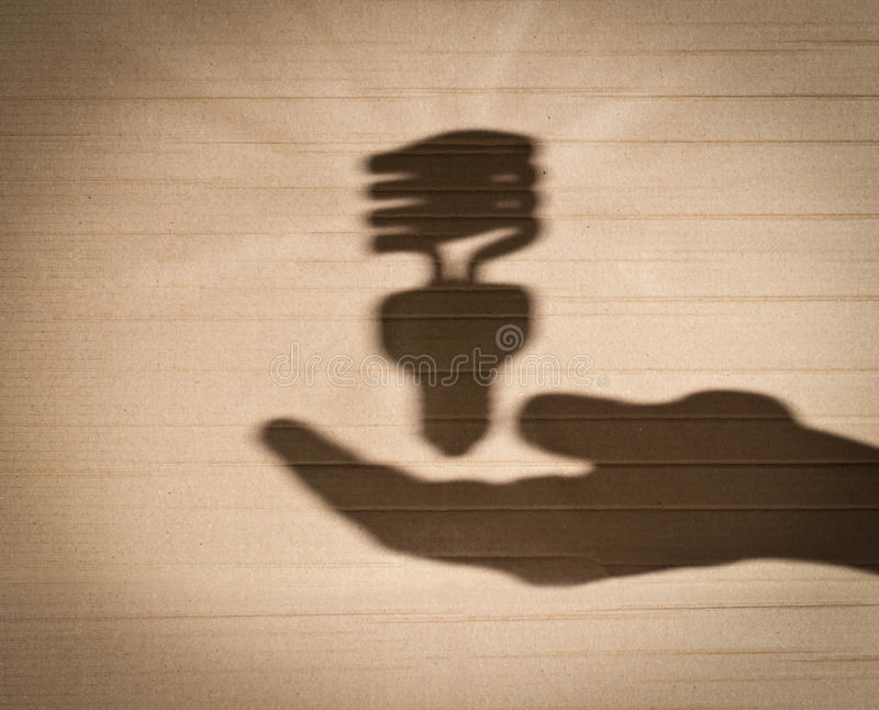 Fluorescent light bulb and human hand. Shadow of human hand holding shadow of fluorescent light bulb against cardboard background royalty free stock photography
