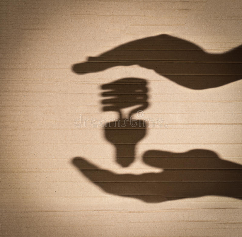 Fluorescent light bulb between human hands. Shadow of human hands holding shadow of fluorescent light bulb against cardboard background stock photos