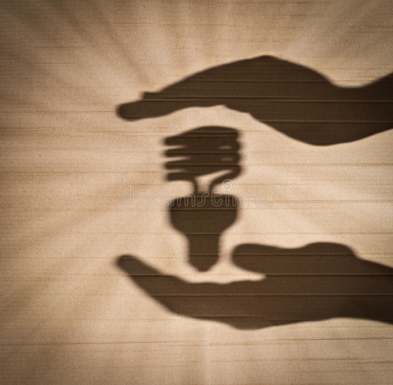 Fluorescent light bulb between human hands. Shadow of human hands holding shadow of fluorescent light bulb against cardboard background royalty free stock photo