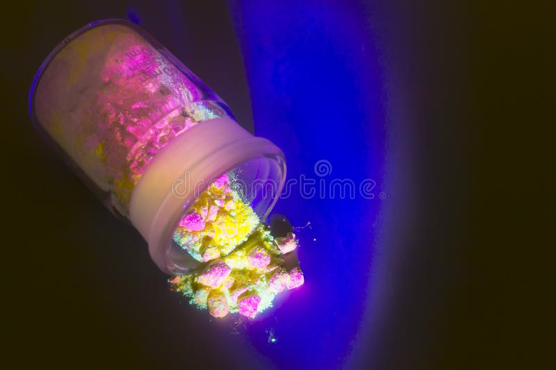Fluorescent organic materials of red, yellow and green color for production OLED inside glass bottle in UV light. Fluorescent organic materials like a powder of royalty free stock photos