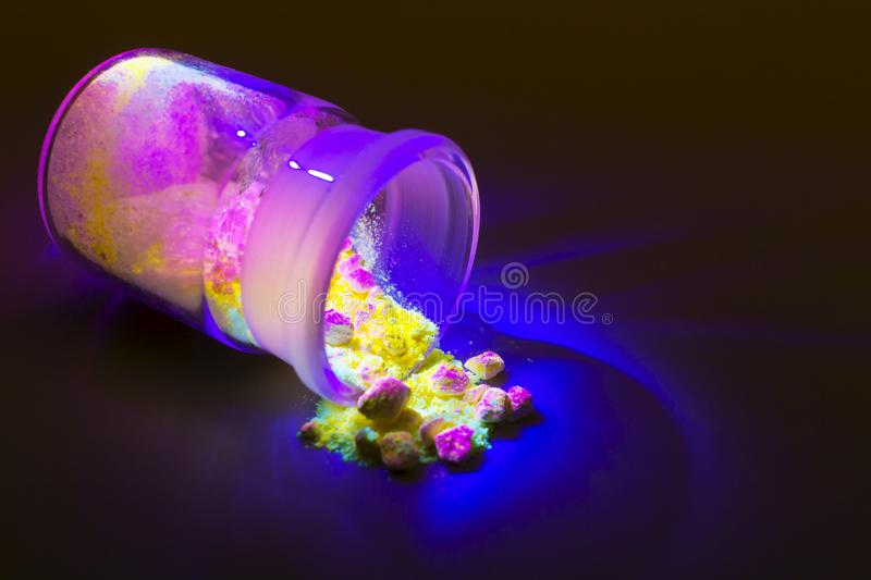 Fluorescent organic materials of red, yellow and green color for production OLED inside glass bottle in UV light. Fluorescent organic materials like a powder of stock images