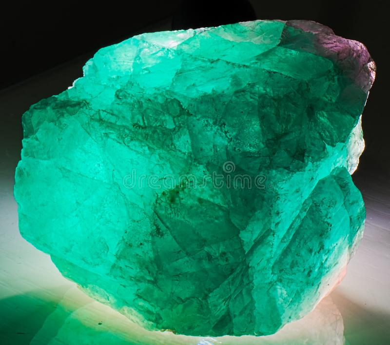 Fluorite mineral stone crystal. Gem, green and magenta shades, transparent, shiny, on white background, lit from behind royalty free stock image