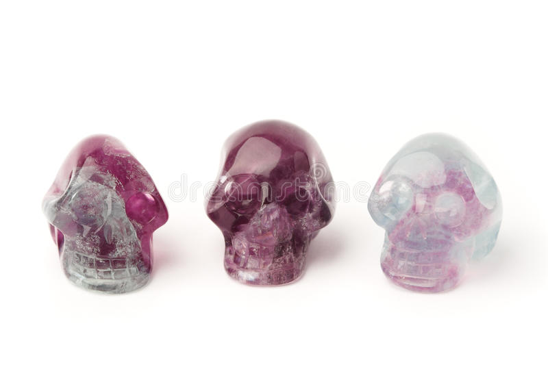 Fluorite skulls. Three hand carved fluorite skulls isolated on white royalty free stock photo
