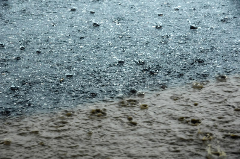 Flurry of rain. Rain pelts down to the street. raindrops are visible. in the foreground there is a muddy puddle stock images