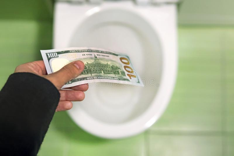 Flush money down the toilet, throws dollar bills in the toilet, loss concept, close up, selective focus. Concept of senseless waste of money, loss, useless royalty free stock image