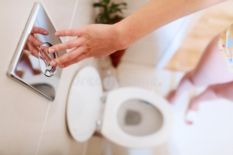 Flushing toilet. A young woman is flushing the toilet