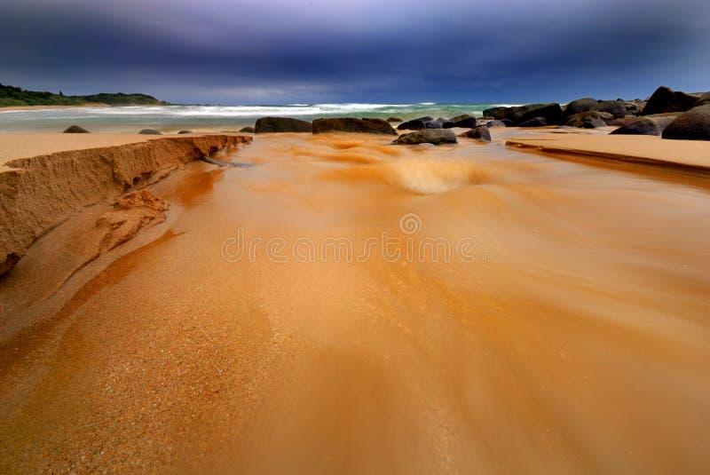 Fluss, der in Meer läuft lizenzfreie stockfotos