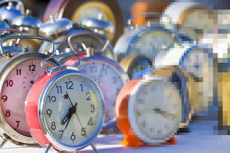 Fluss der Zeit ist gerade eine Illusion - Konzeptbild mit alten farbigen Metalltischuhren lizenzfreies stockbild