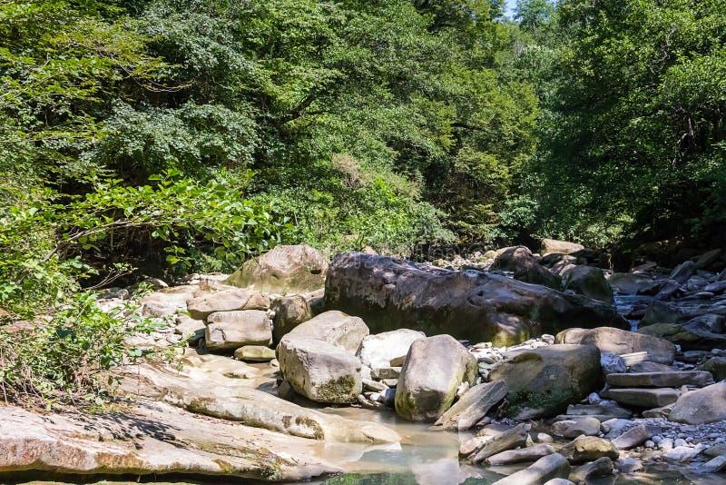 Fluss mit einem Stapel von großen glatten Steinen und von pebbled Ufern der Anfang des Wasser ` s Weges auf einem hellen Sommerta lizenzfreies stockbild