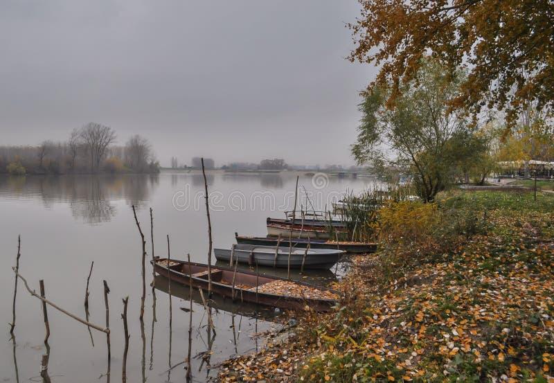 Fluss mit gebundenen Booten am Herbst November-Grautag stockbild