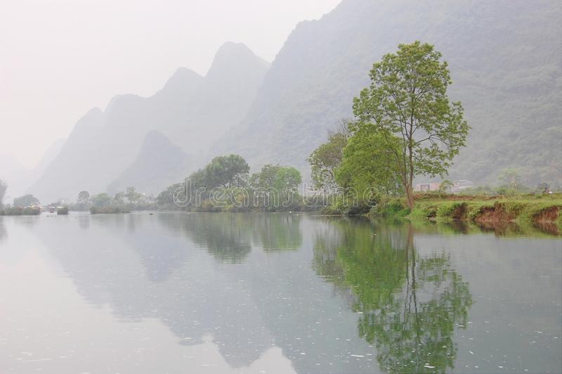 Fluss und Berg im nebelhaften stockfotografie