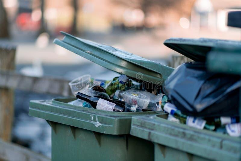 Flussi dei rifiuti fuori da un recipiente verde nel Regno Unito dopo un fine settimana di bere nel distretto del lago, Cumbria fotografia stock libera da diritti