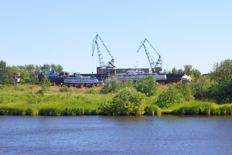 Flussküstenlinie mit Gras, Schiffen und Kränen für das Laden stockbilder