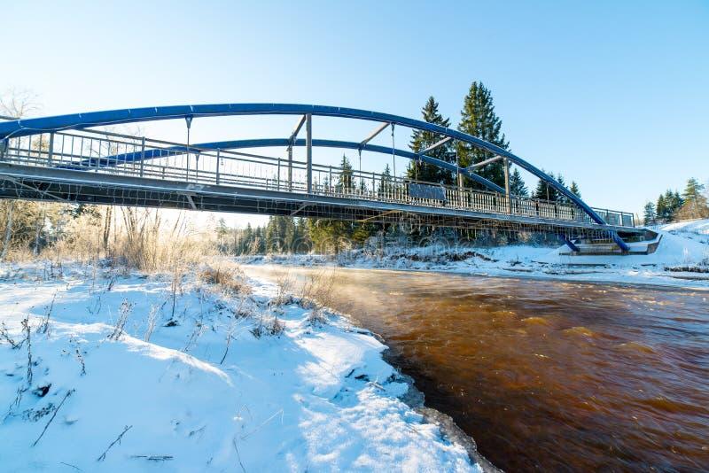 Flusslandschaft des verschneiten Winters mit Metallbrücke lizenzfreie stockfotografie