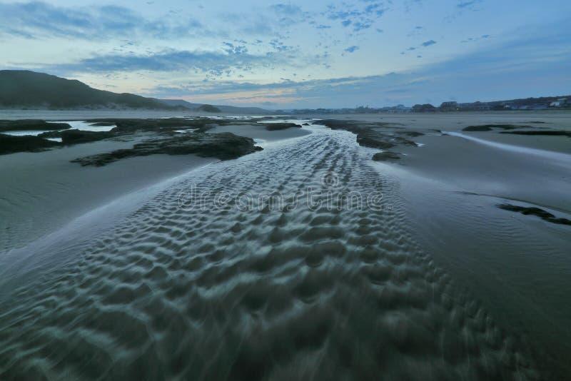 Flusso continuo delle acque alle rocce del nero del trhough di tramonto immagini stock
