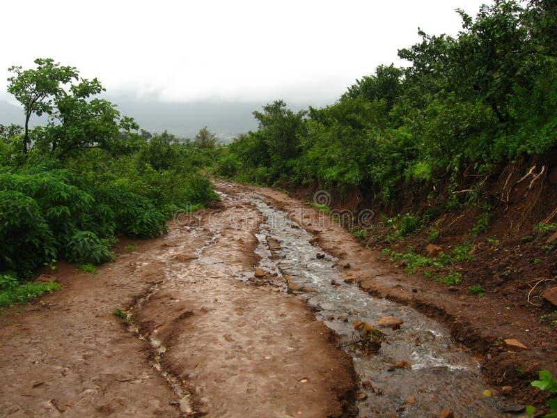Flusso e strada non asfaltata fangosi immagini stock