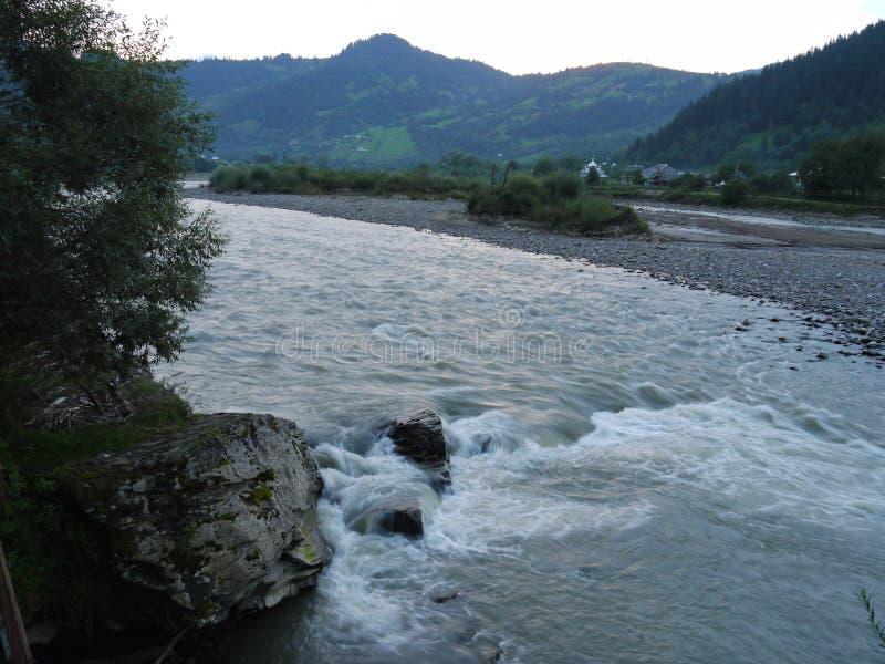 Flusso veloce e rapido del fiume contro il contesto delle case del villaggio al piede di grande montagna immagini stock