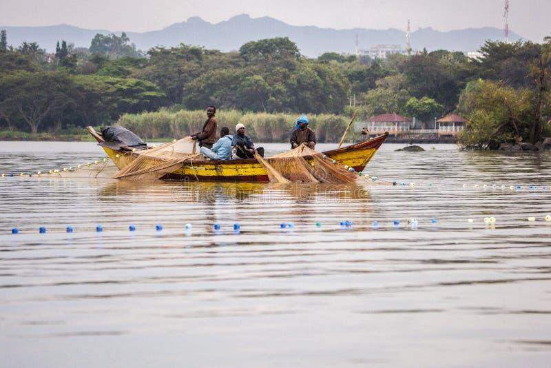 Flusspferd-Punkt Sept. 2017 17, Kisumu, Viktoriasee, Kenia Junge afrikanische Fischer im alten hölzernen Fischenkanu, holen in di lizenzfreie stockbilder