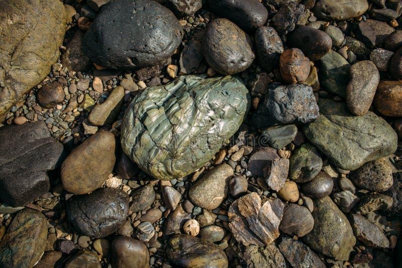 Flusssteine glitzern in der Sonne Große grau-grüne Kopfsteine einer von kleinen bunten Kieseln Konzept des Steinhintergrundes stockfoto