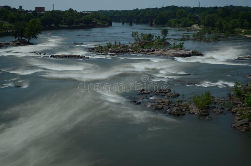 Flussstromschnellen in der Bewegung mit Holz und im Grün um es stockfoto