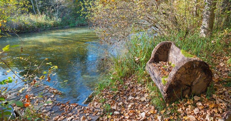 Flussufer mit rustikaler Bank im Herbst stockbild