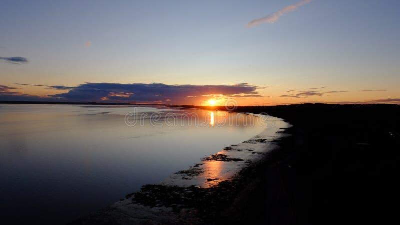 Flussufer-Sonnenuntergang lizenzfreies stockfoto