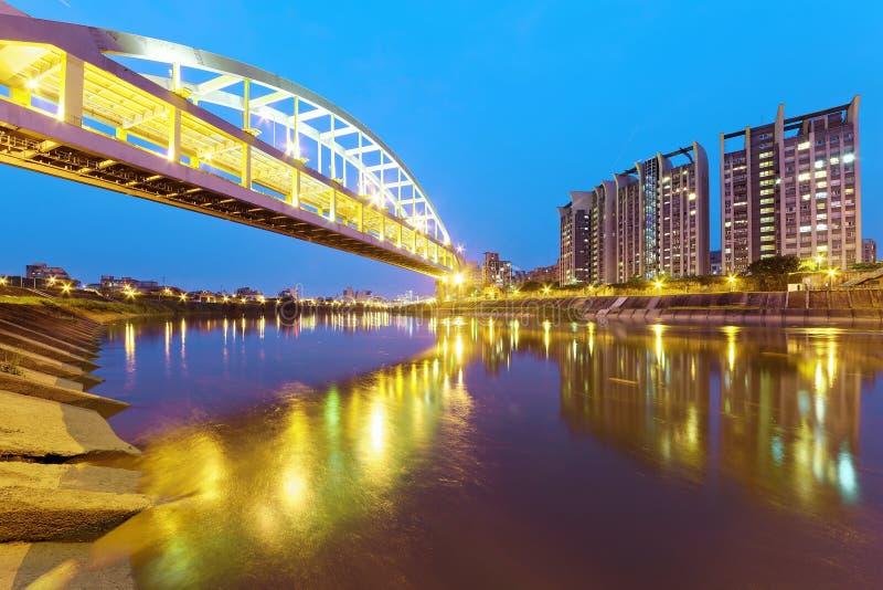 Flussufergebäude und die berühmte HuanDong-Regenbogen-Brücke über Keelungs-Fluss an der Dämmerung in Taipeh Taiwan stockfotografie
