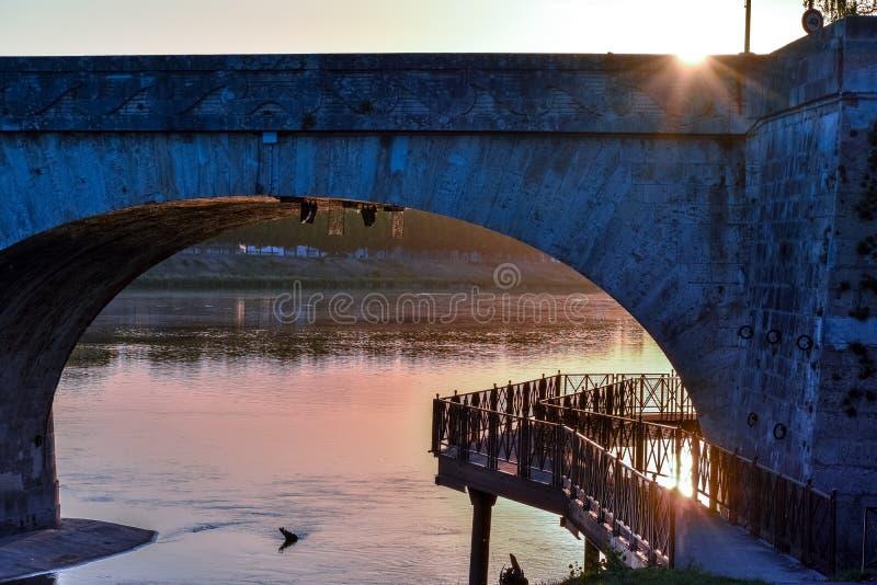 Flussuferweg in einer bunten Sonnenunterganghintergrundbeleuchtung stockbilder