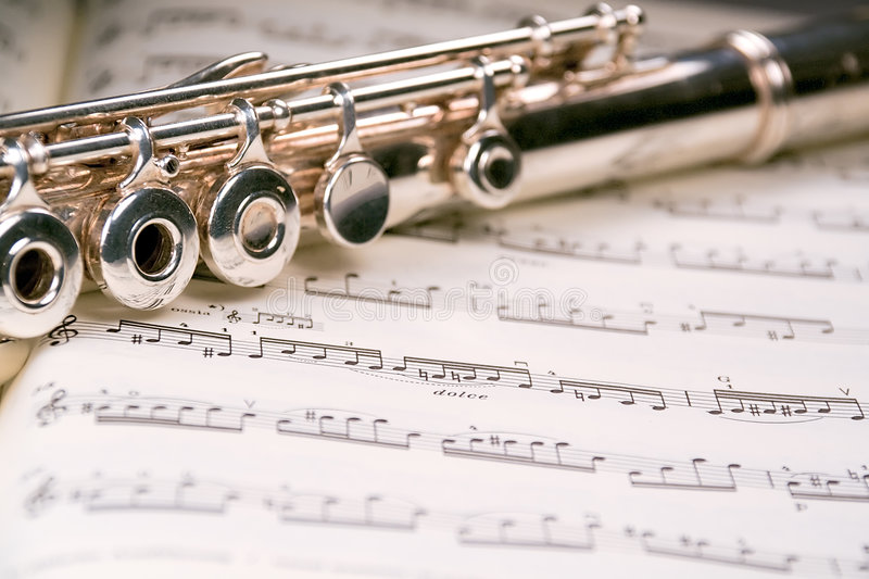 Flute across a musical score royalty free stock images