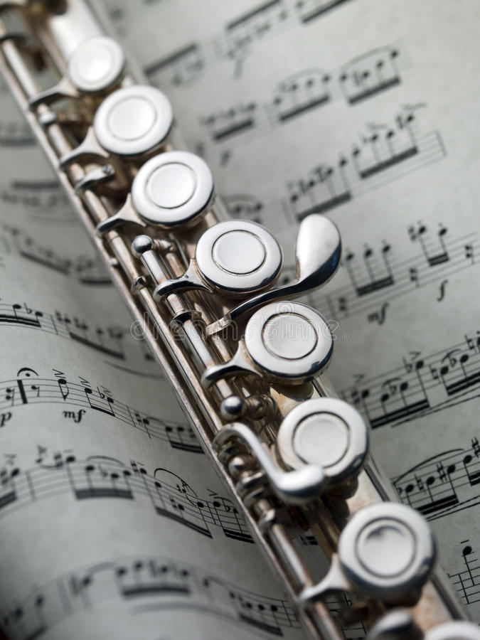 Flute on musical score royalty free stock image