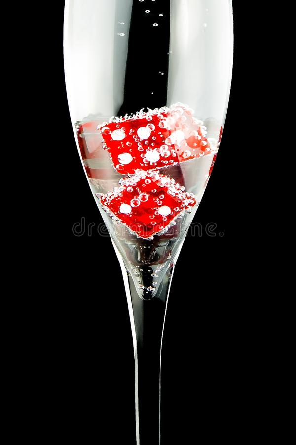 Flute with two red dice and a lot of bubbles stock photo