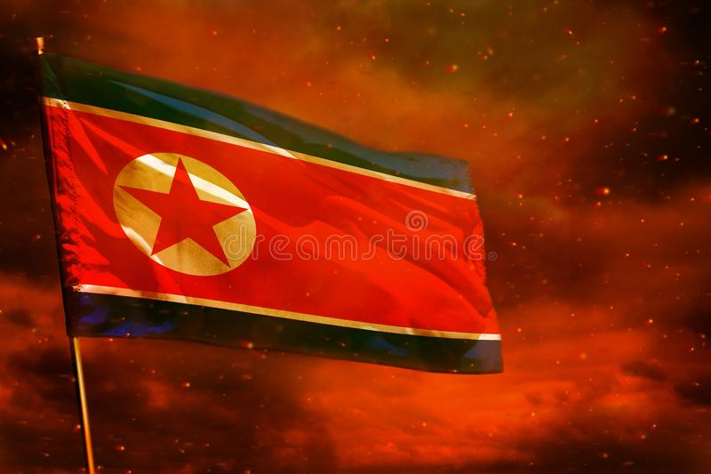 Fluttering Democratic Peoples Republic of Korea North Korea flag on crimson red sky with smoke pillars background. Troubles. Fluttering Democratic Peoples stock image